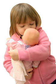 Toddler hugging doll
